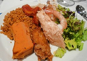 A sample of traditional African Food - Jollof rice served with moi-moi, shrimp and fish with salad.